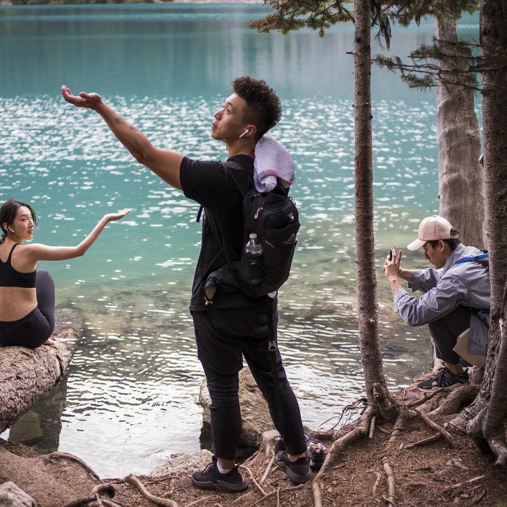 Des touristes tendent la main vers le ciel afin de percevoir s'il pleut aux abords d'un lac du parc britanno-colombien Joffre Lakes pendant qu'un autre prend une photo.