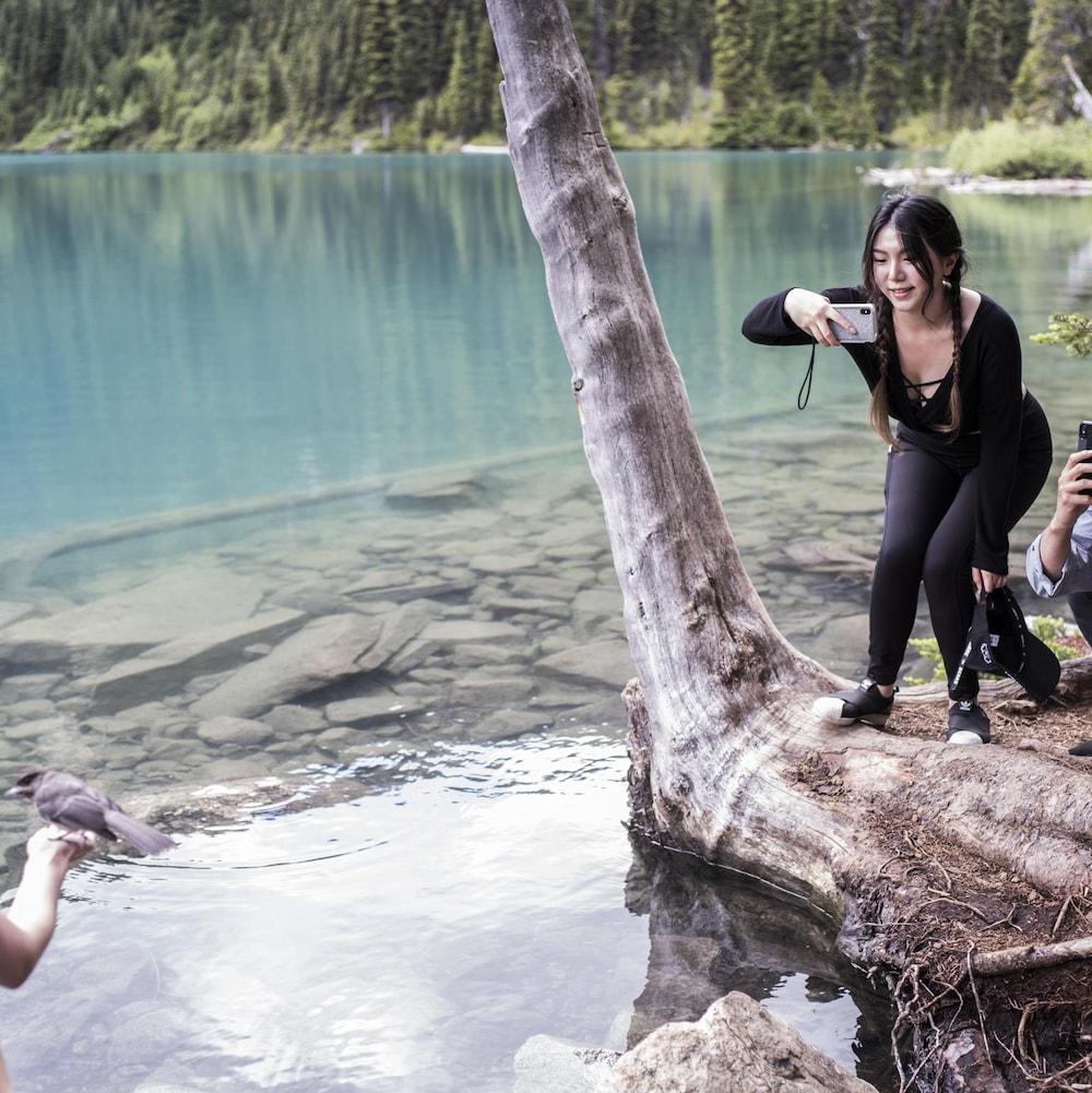 Deux touristes prennent une photo de leur amie qui tient un oiseau dans sa main aux abords d'un lac du parc britanno-colombien Joffre Lakes.