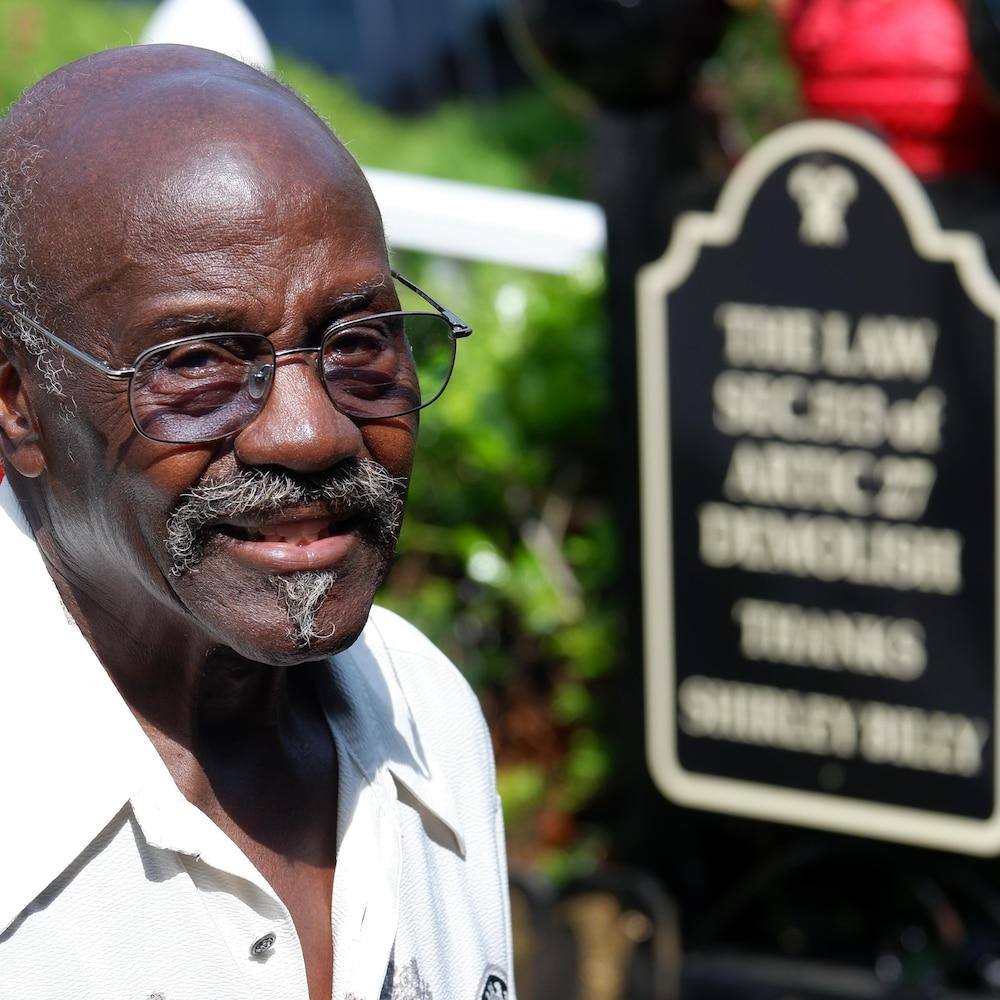 John Billy, devant un signe qui rend hommage à sa femme, autour de la maison familiale à Baltimore.