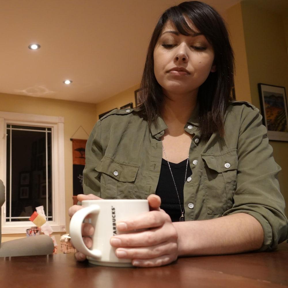 Une jeune femme dans la fin vingtaine tient une tasse dans ses mains et elle est assise à une table le regard vers sa tasse.
