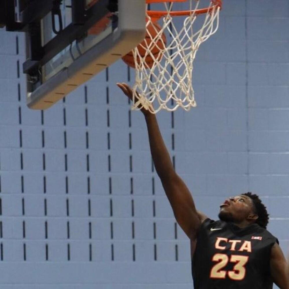 Kevin met le ballon dans le panier de basketball.