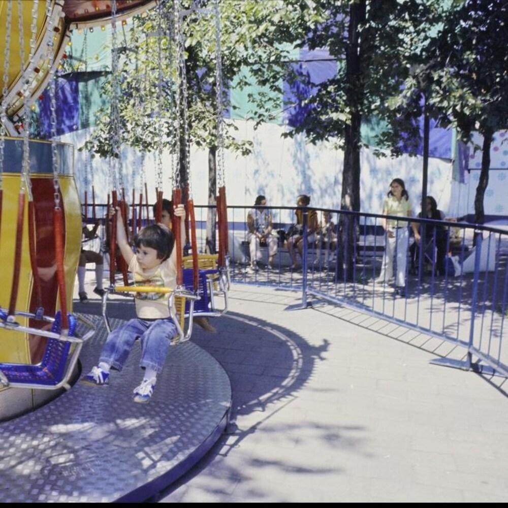 Enfants s'amusant dans un manège de balançoires à La Ronde.