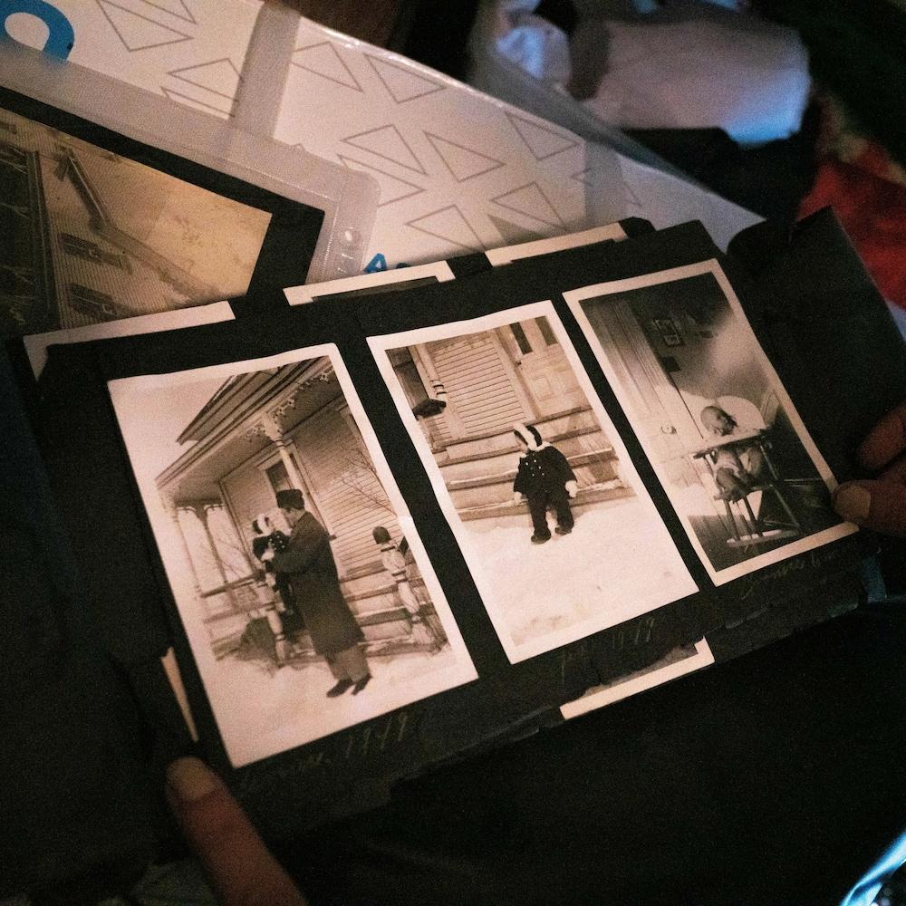 Des photos en noir et blanc d'enfants se tenant devant la maison familiale sont collées dans un album photo.