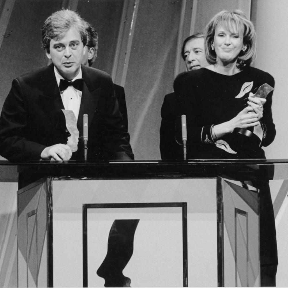 Simon Durivage et madeleine Poulin qui tiennent dans leur mains un trophée Gémeaux. Simon Durivage prononce un discours de remerciements.