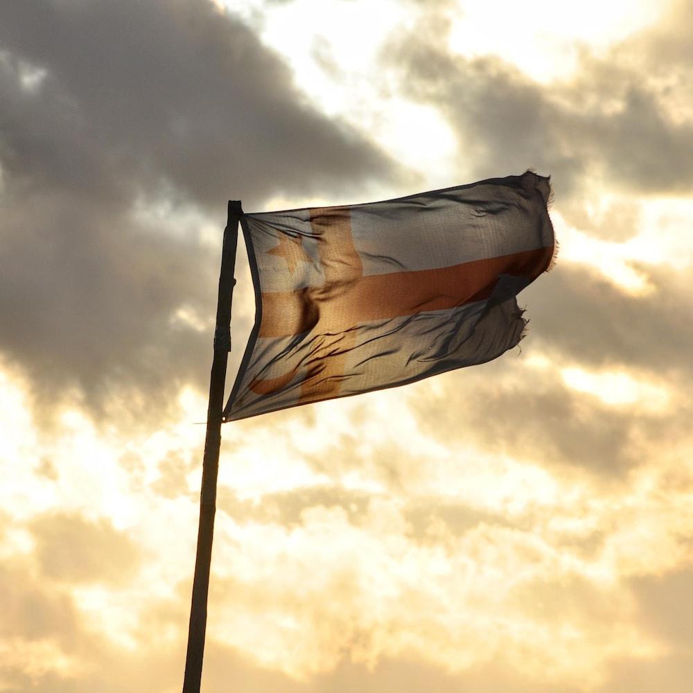 Le drapeau du peuple micmac qui flotte dans le ciel alors que le soleil se lève.