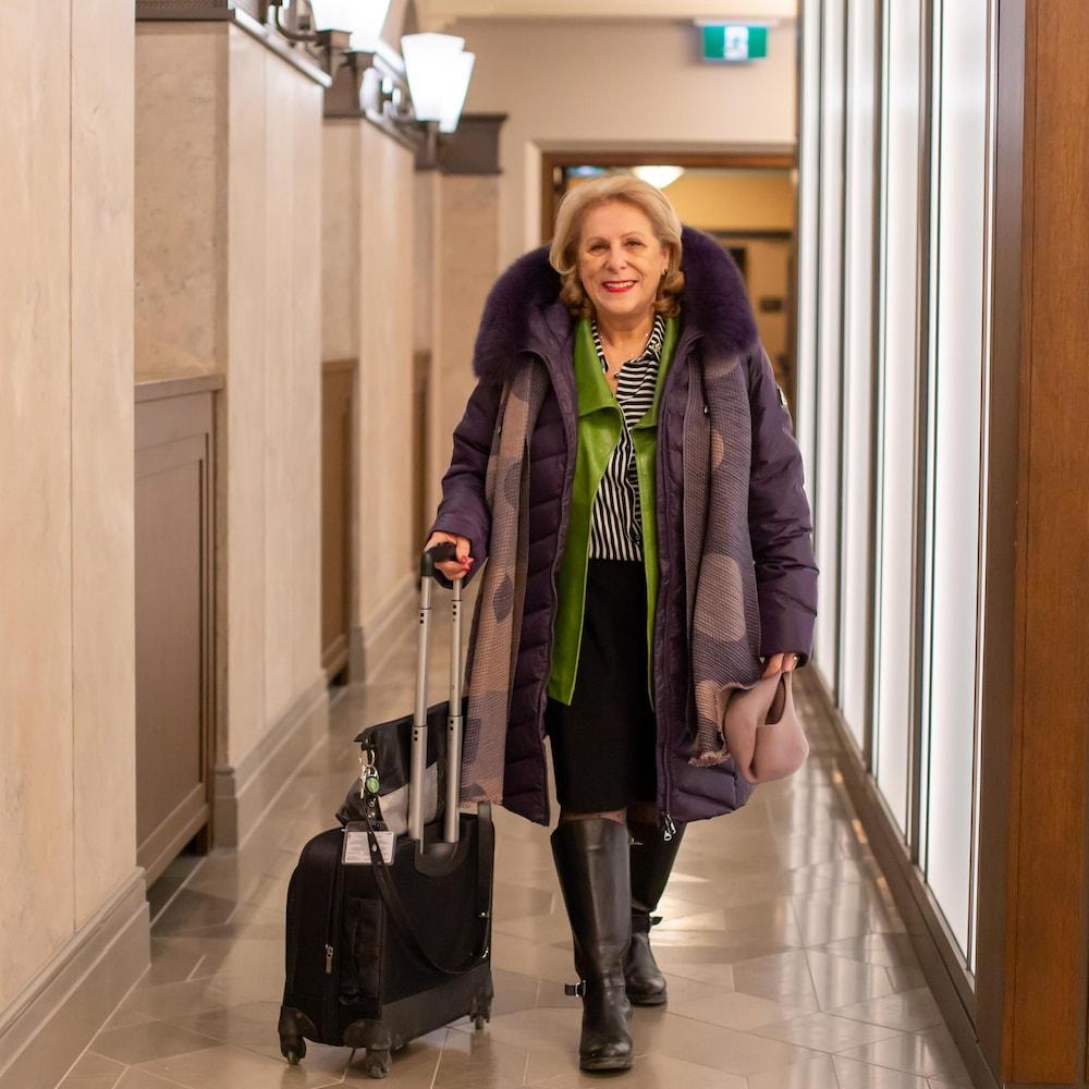 La députée avec son manteau et sa valise sur roulettes dans un corridor du parlement temporaire à Ottawa.