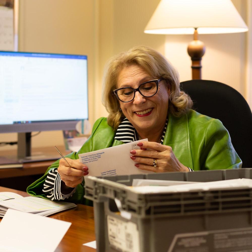 La députée qui ouvre une lettre à son bureau d'Ottawa.