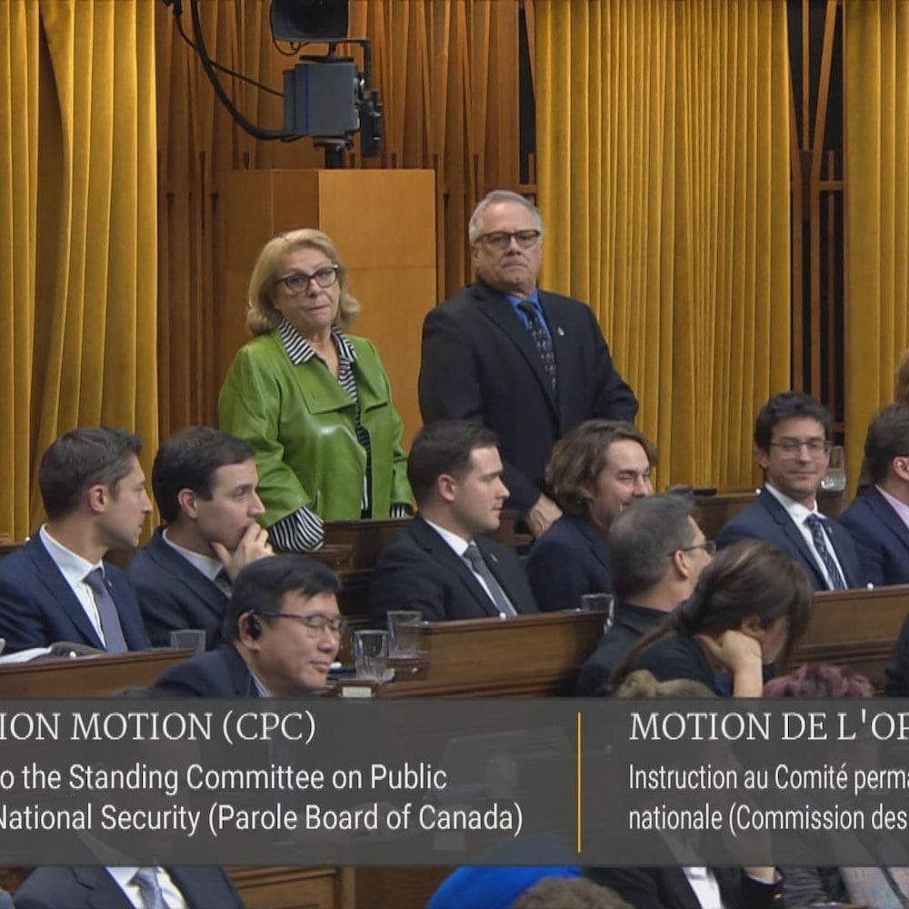 La députée debout qui vote, entourée de ses collègues à la Chambre des communes.