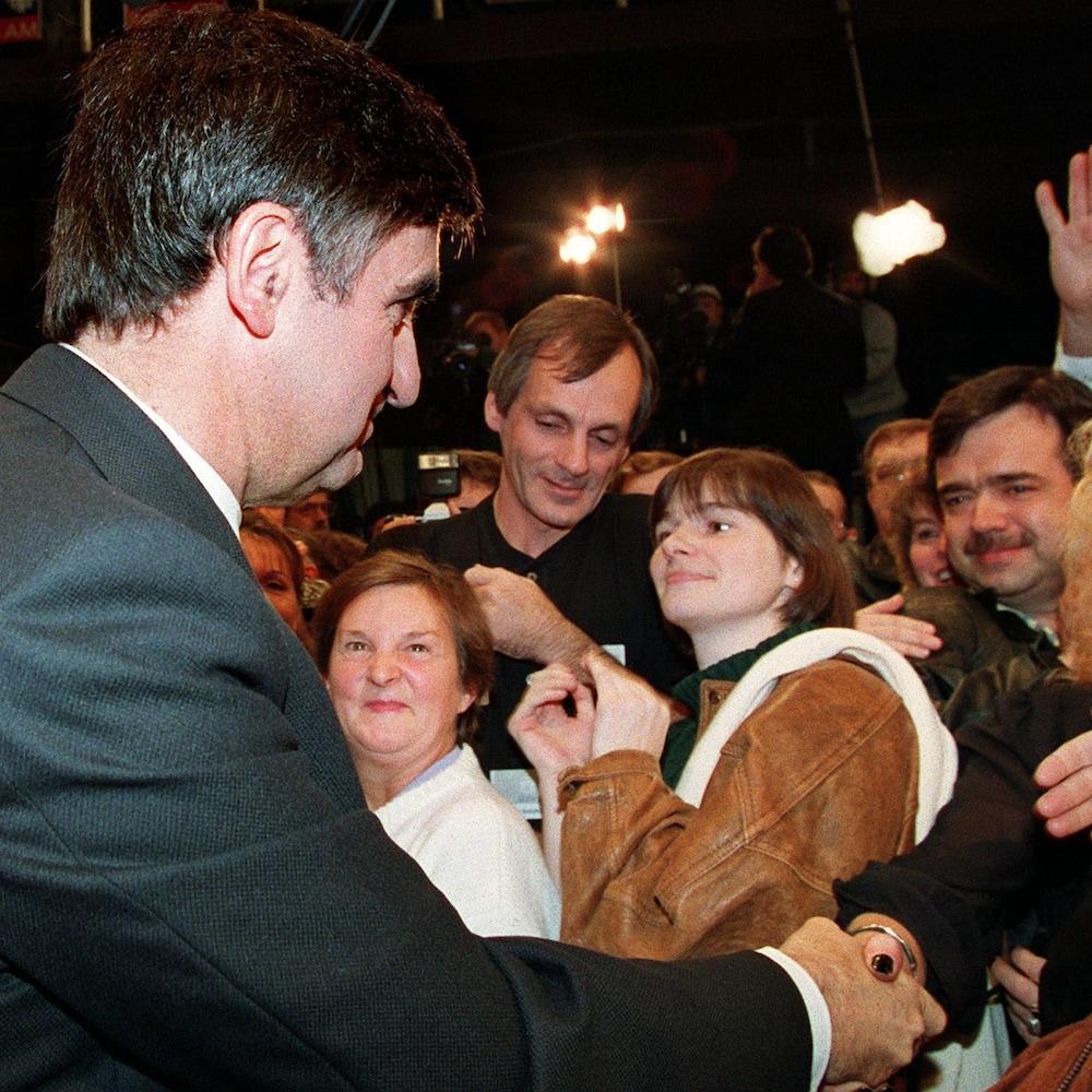 Lucien Bouchard donne la main à une dame lors d'un rassemblement tenu à Alma.