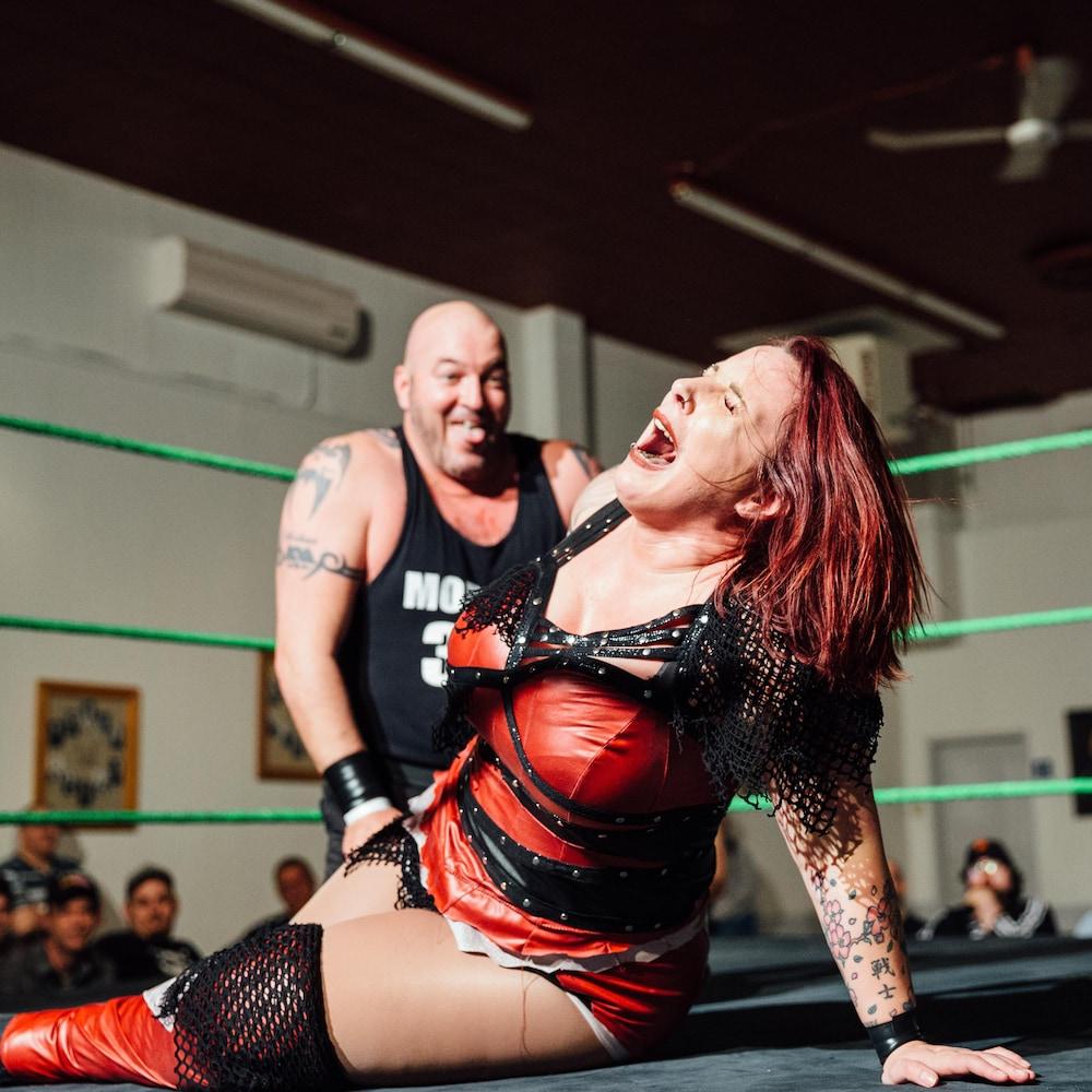 Pendant que la lutteuse semble se tordre de douleur sur le ring, son adversaire la regarde en souriant et en faisant la grimace.