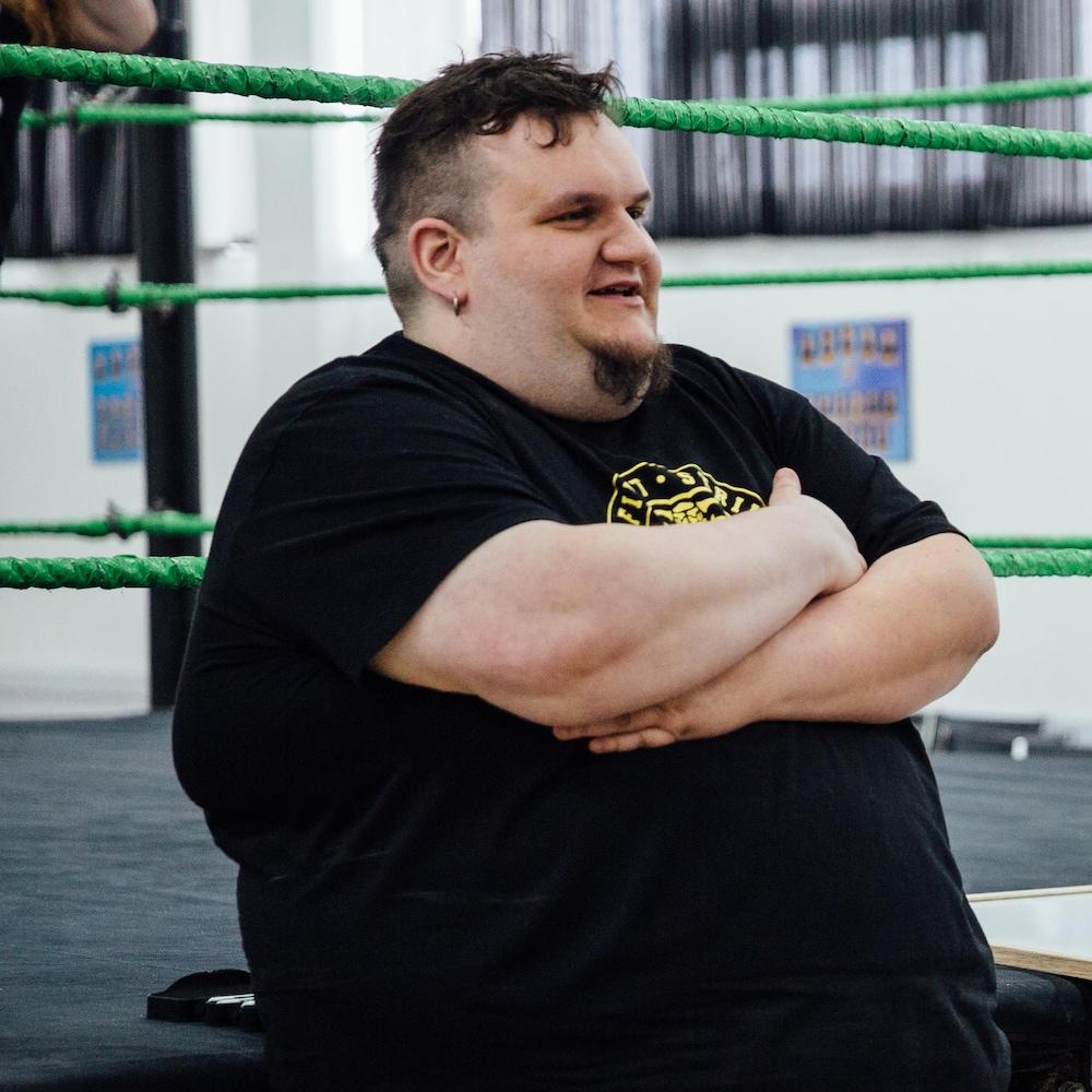 L'homme a le dos appuyé sur un ring de lutte, les bras croisés.