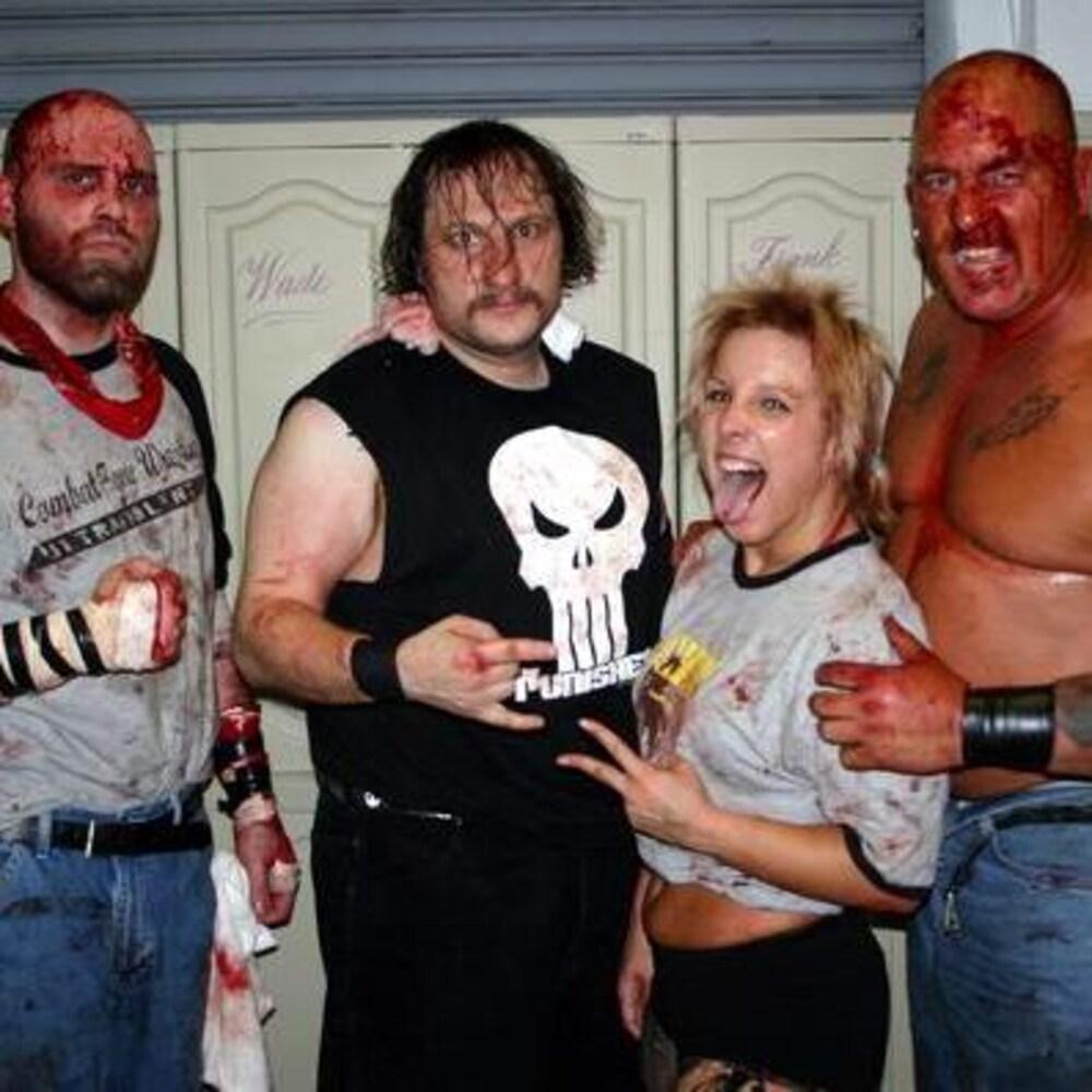 Les quatre personnes sont couvertes de sang et posent pour la caméra.