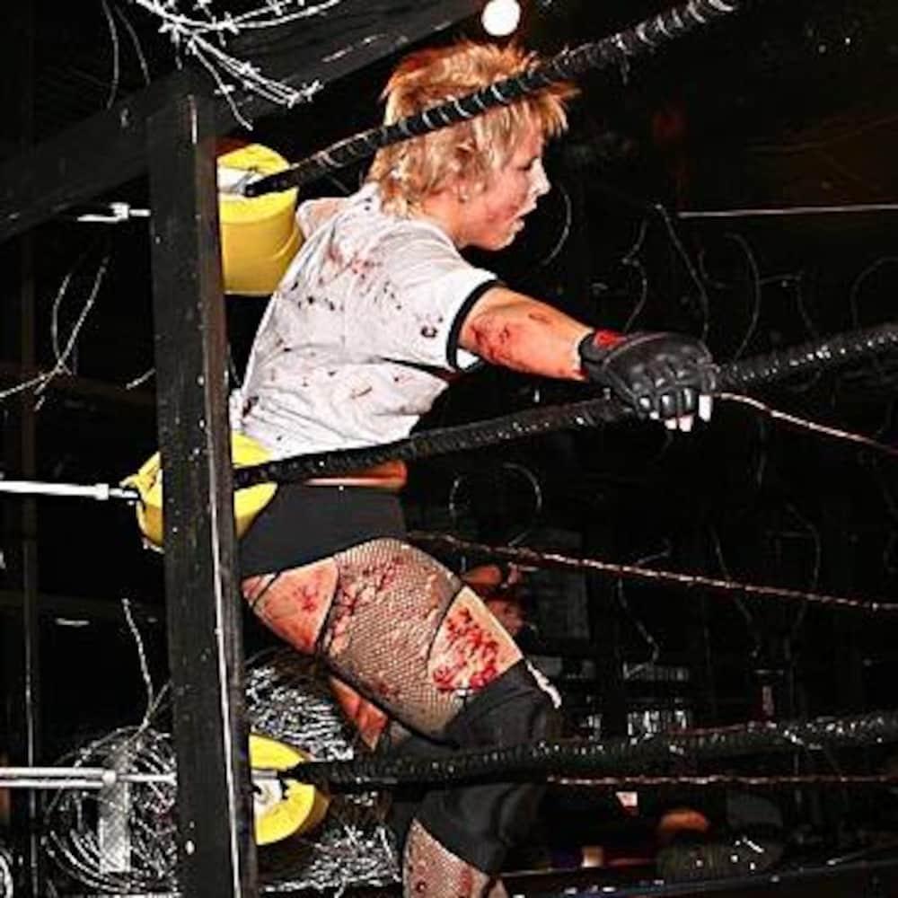 La lutteuse est appuyée sur les cordes du ring, entourée de barbelés et est couverte de sang.