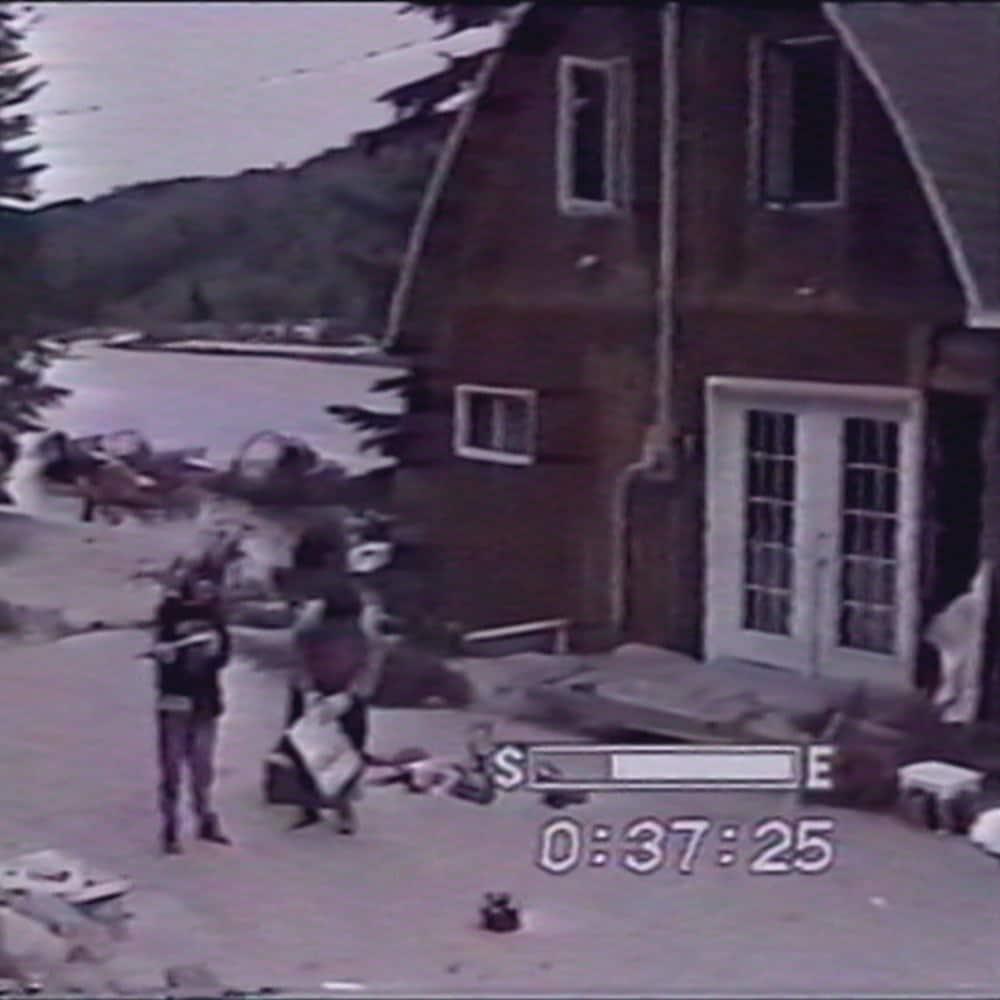 Deux personnes devant une maison.