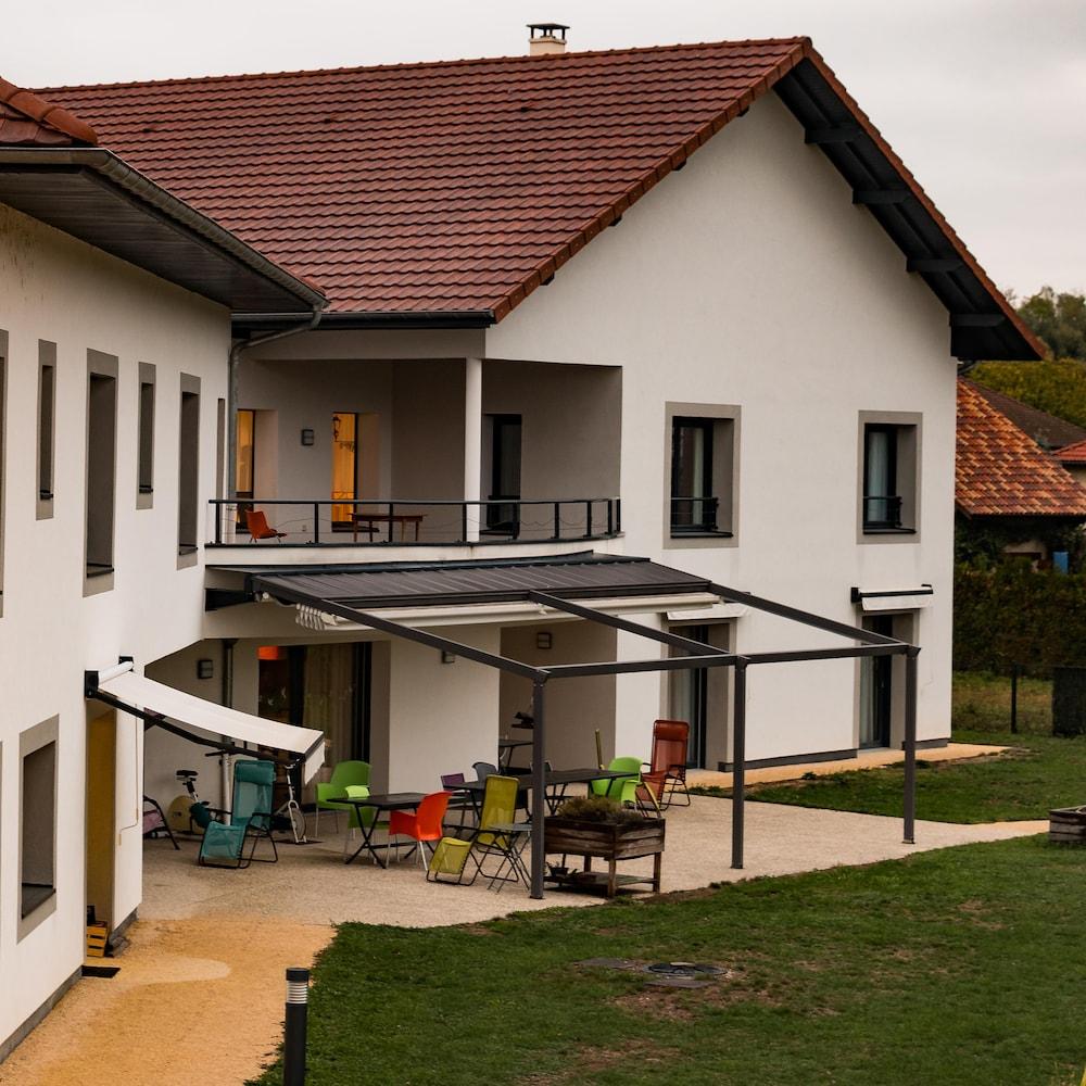 Chaises sur une terrasse, derrière un des deux Maisons de Crolles