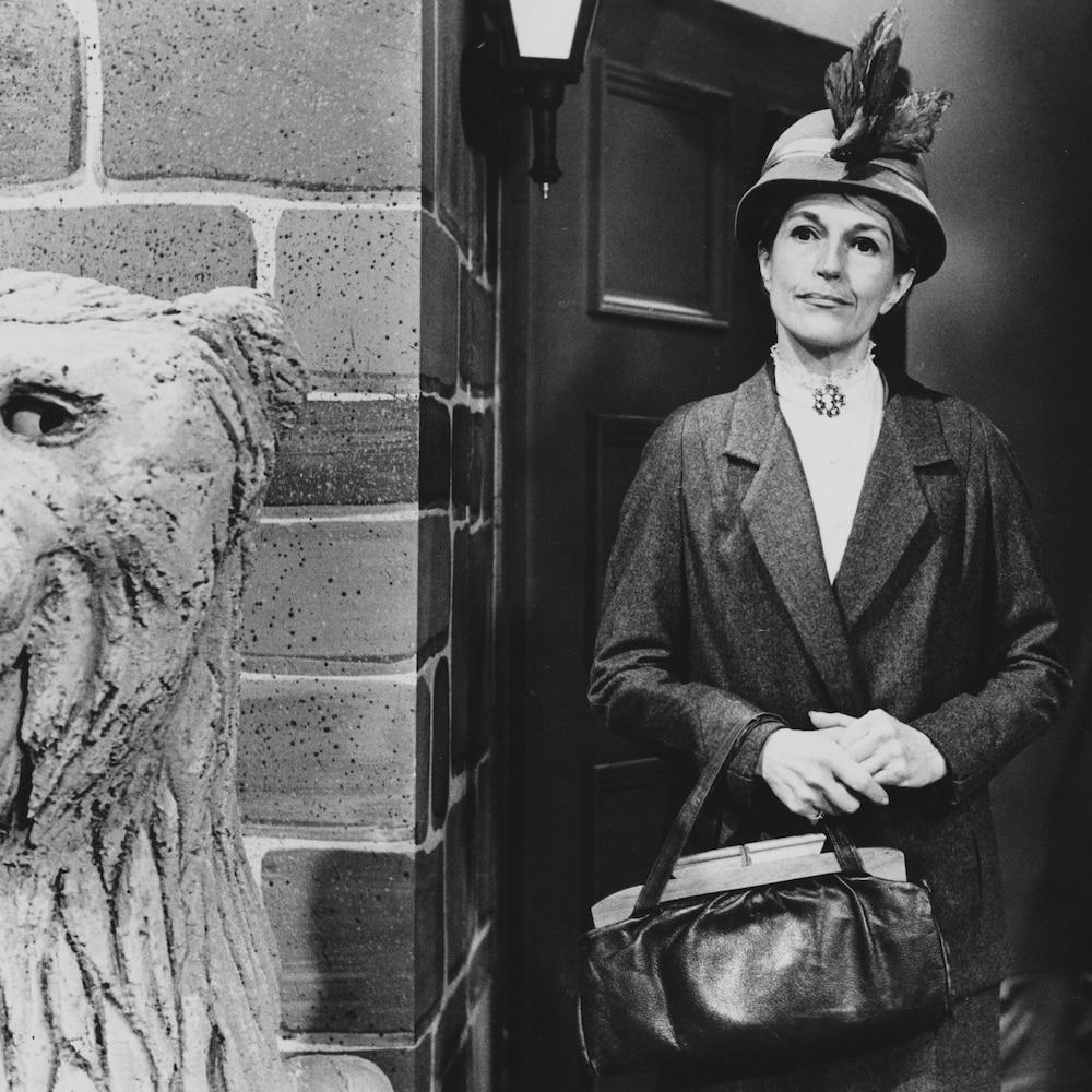 Pénélope, avec son chapeau et son manteau, sortant d'une résidence.