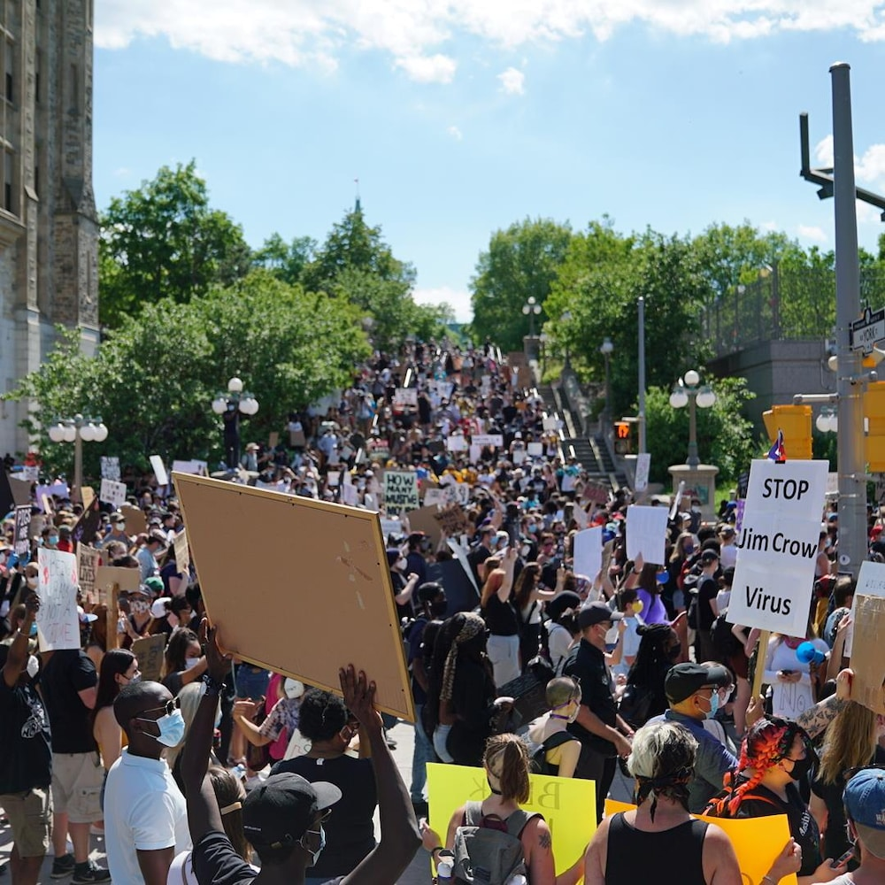 Des centaines de personnes brandissent des pancartes devant l'ambassade sur la promenade Sussex.