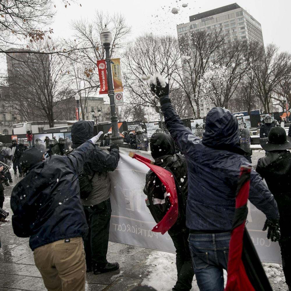 Un manifestant lance une balle de neige aux policiers.
