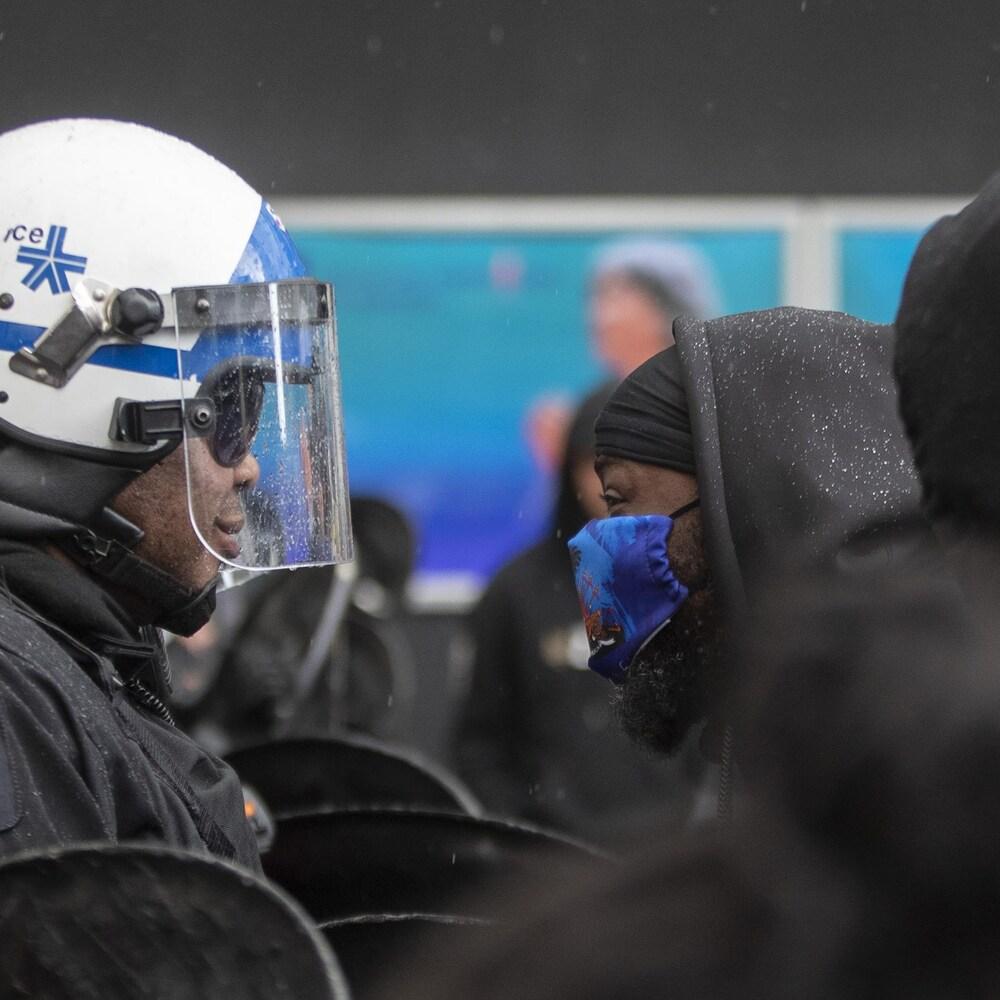 Un manifestant est face-à-face avec un policier en tenue antiémeute.