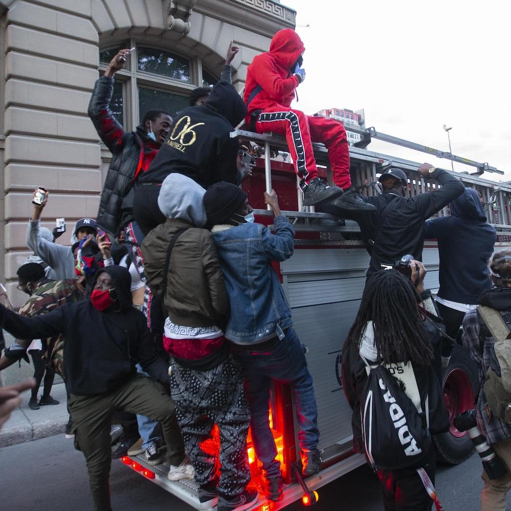 Plusieurs manifestants sur un camion de pompier qui roule dans le centre-ville de Montréal.