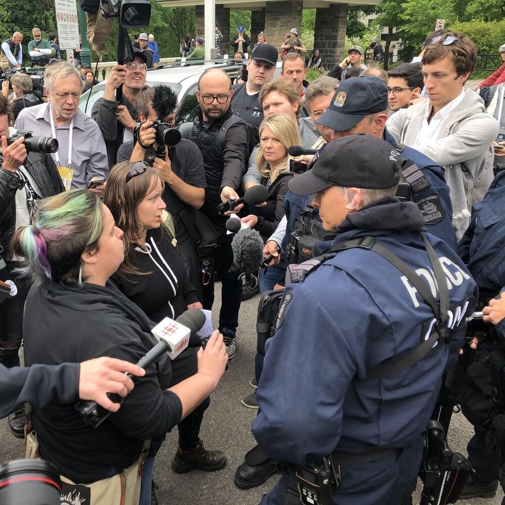 Trois policiers discutent avec deux manifestantes. Ils sont entourés de plusieurs journalistes et photographes.