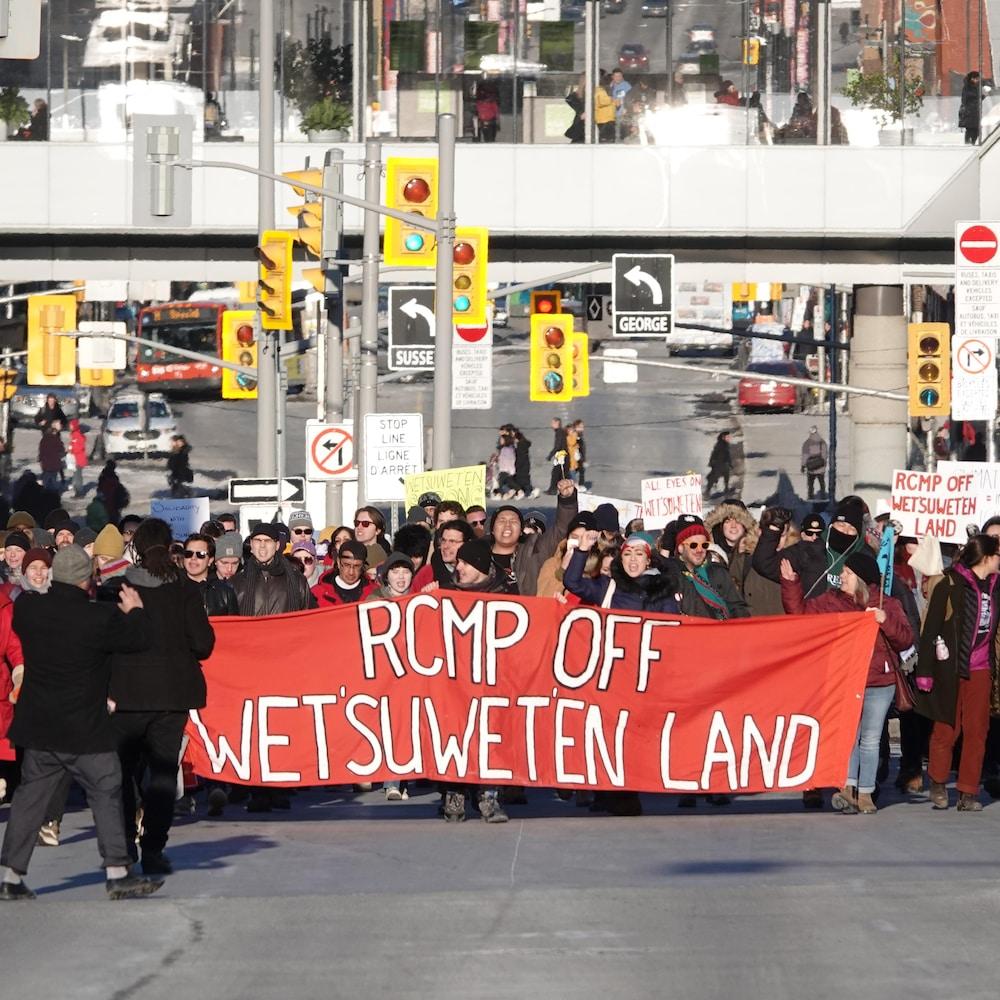 Des manifestants marchant derrière une bannière sur la rue Wellington, à Ottawa, en hiver.