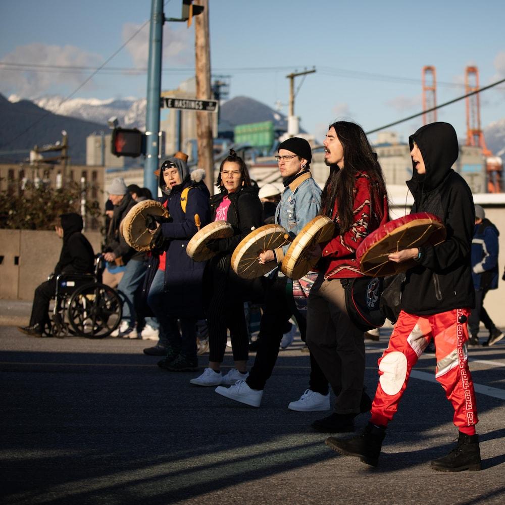 Des manifestants marchent avec des tambours traditionnels.