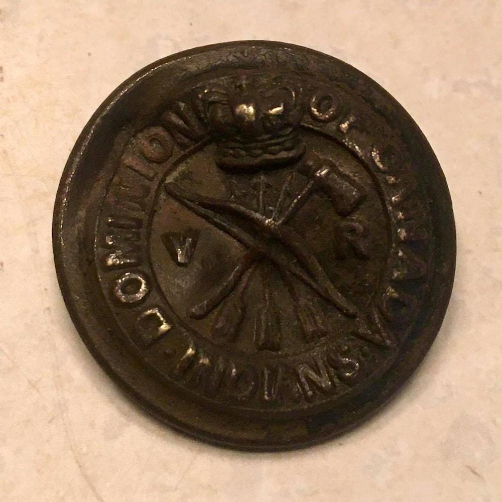 Un bouton de manteau en métal avec gravé dessus un tomahawk et des flèches.