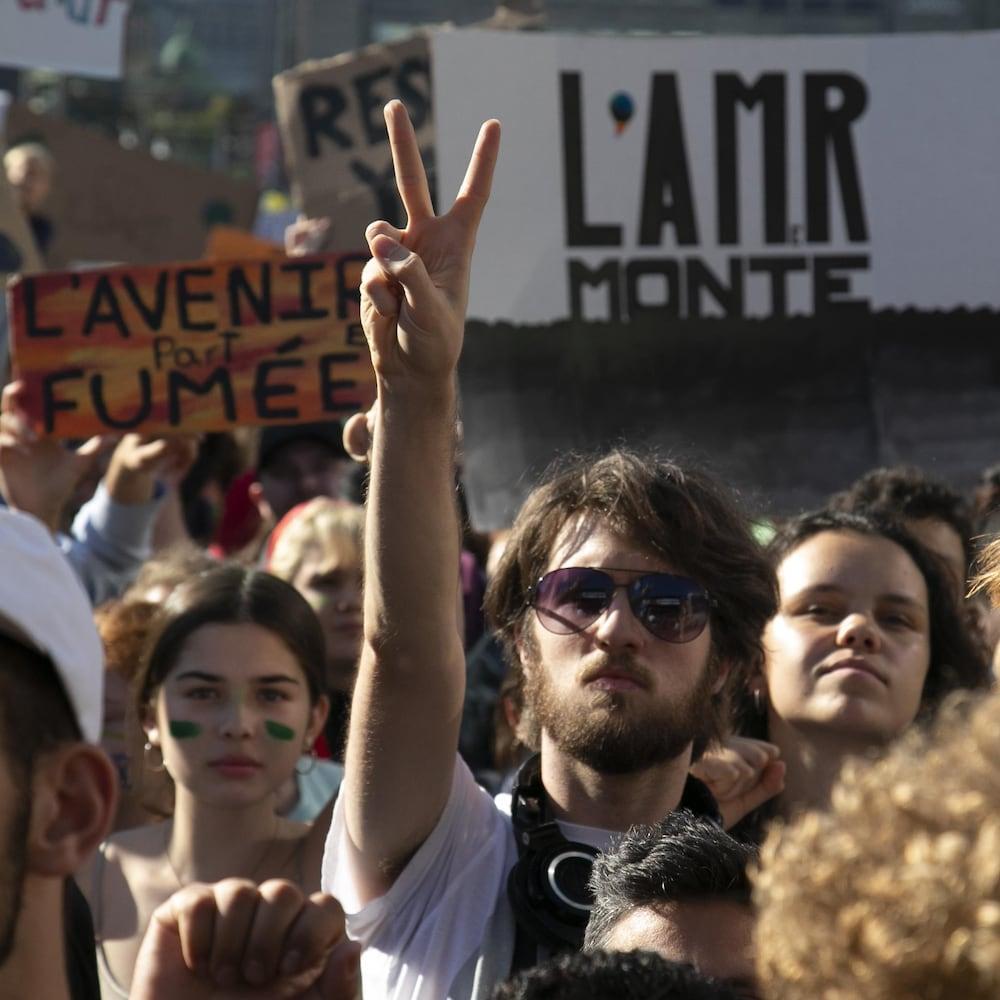 Un manifestant, noyé dans la foule, fait le V de la victoire.