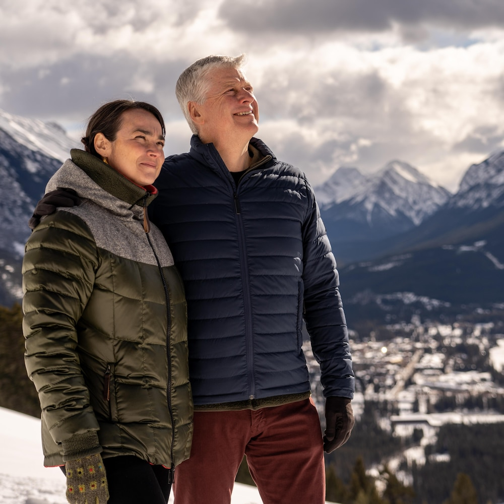 Une femme dans la quarantaine et un homme dans la cinquantaine en habits d'hiver posent devant un décor magnifique de sommets de montagne. Ils sont souriants et leur regard est vers le ciel.