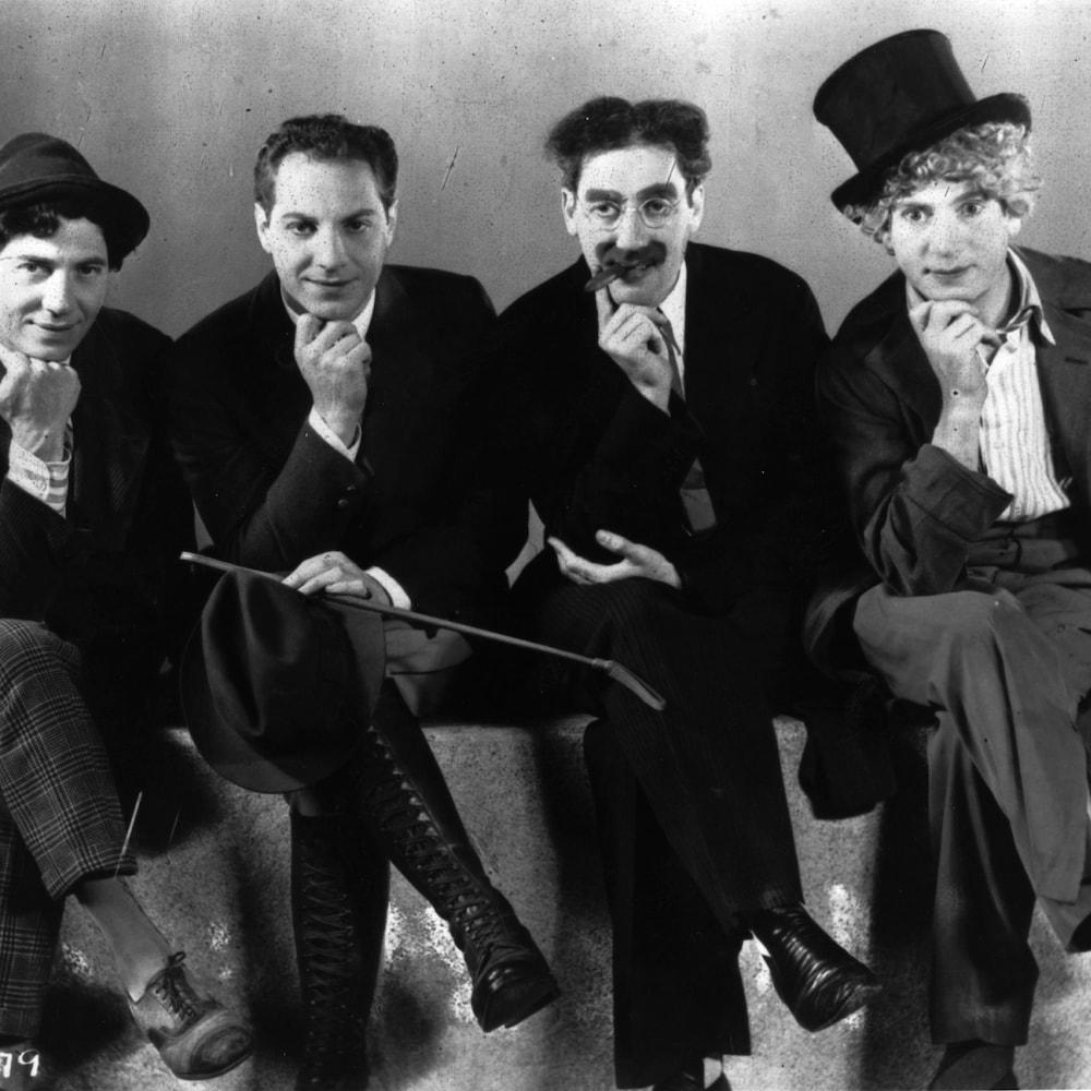 Les quatre frères sont assis sur un banc et posent leur mention dans leur main droite.