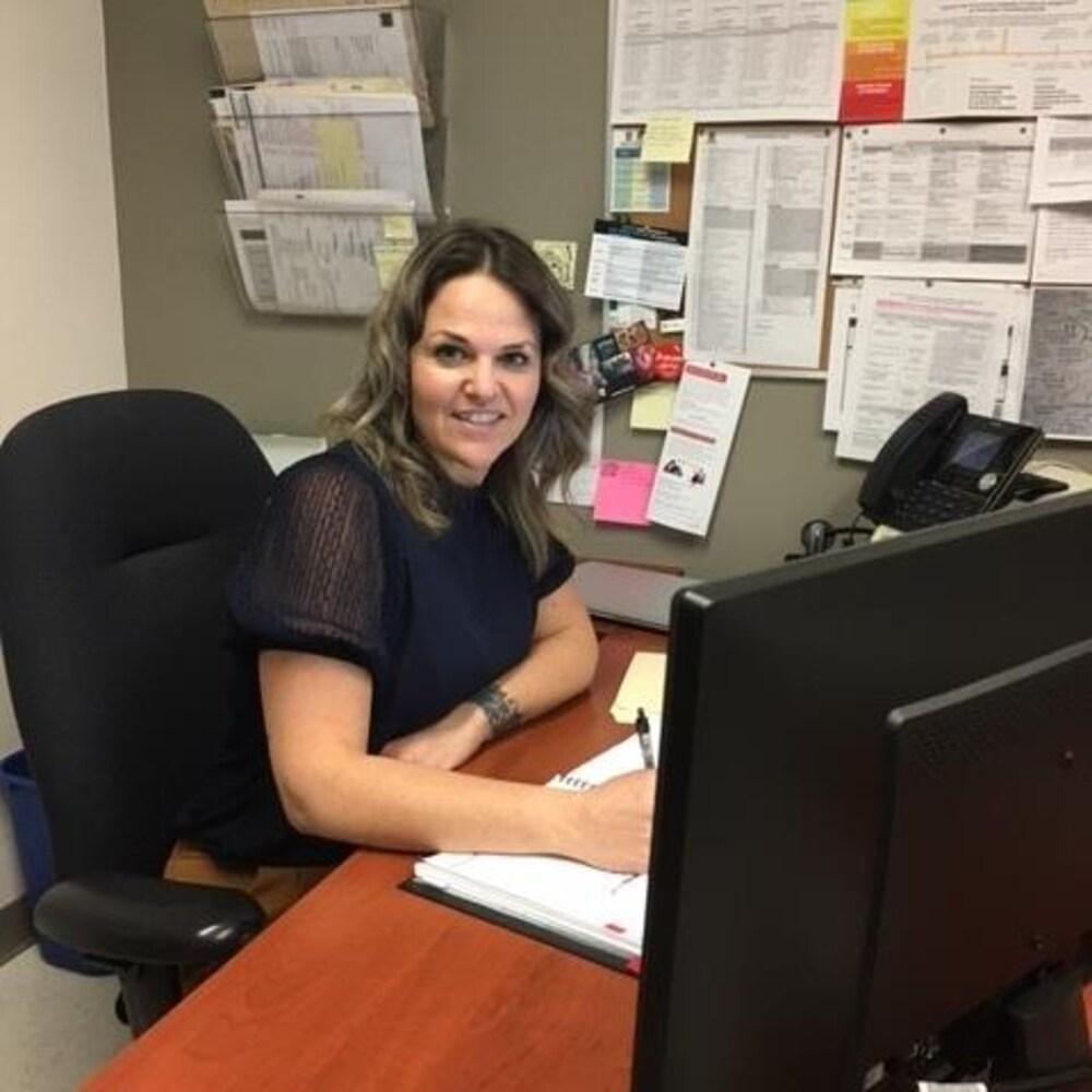 Marylène Ménard assise à son bureau devant un ordinateur, en souriant à la caméra.