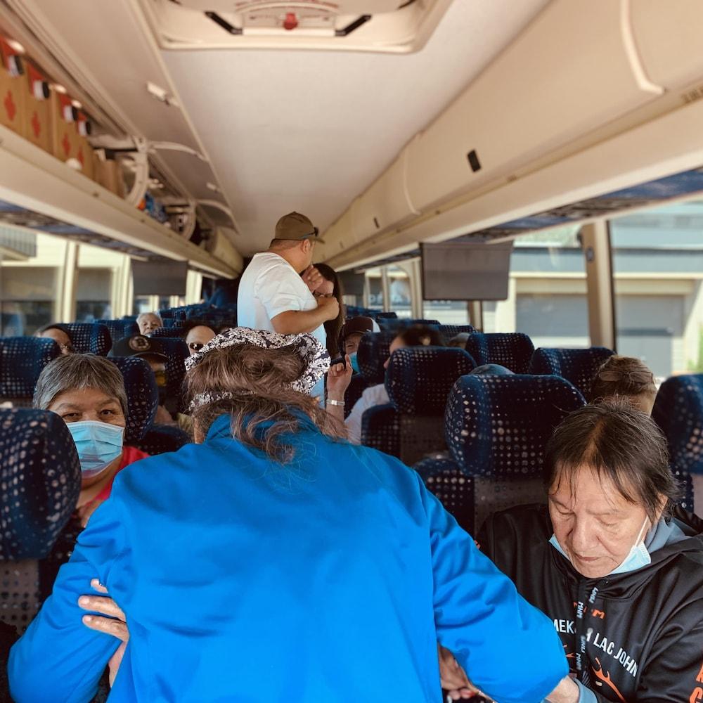 Deux aînés soutiennent le bras d'une autre aînée qui embarque dans l'autobus dans lequel se trouvent d'autres personnes.
