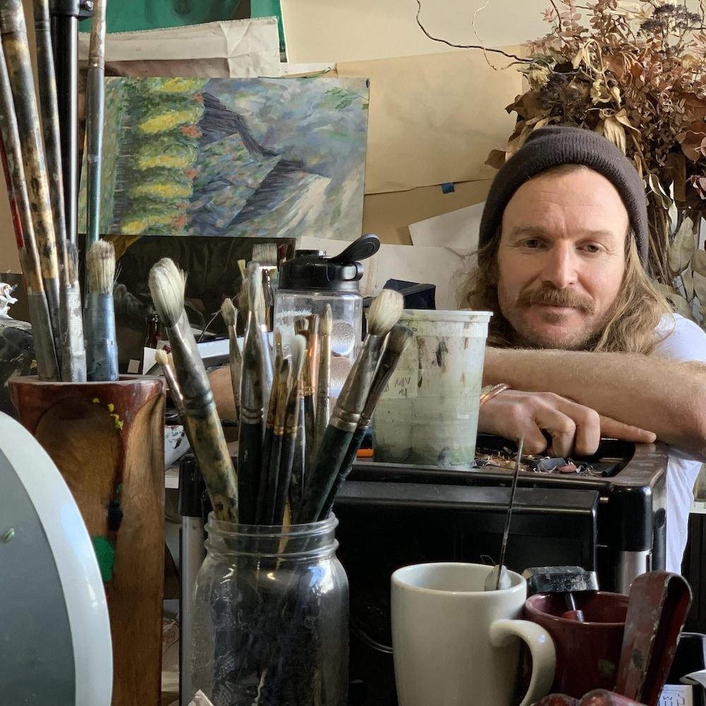 Un jeune homme dans un atelier rempli de matériel d'artiste.