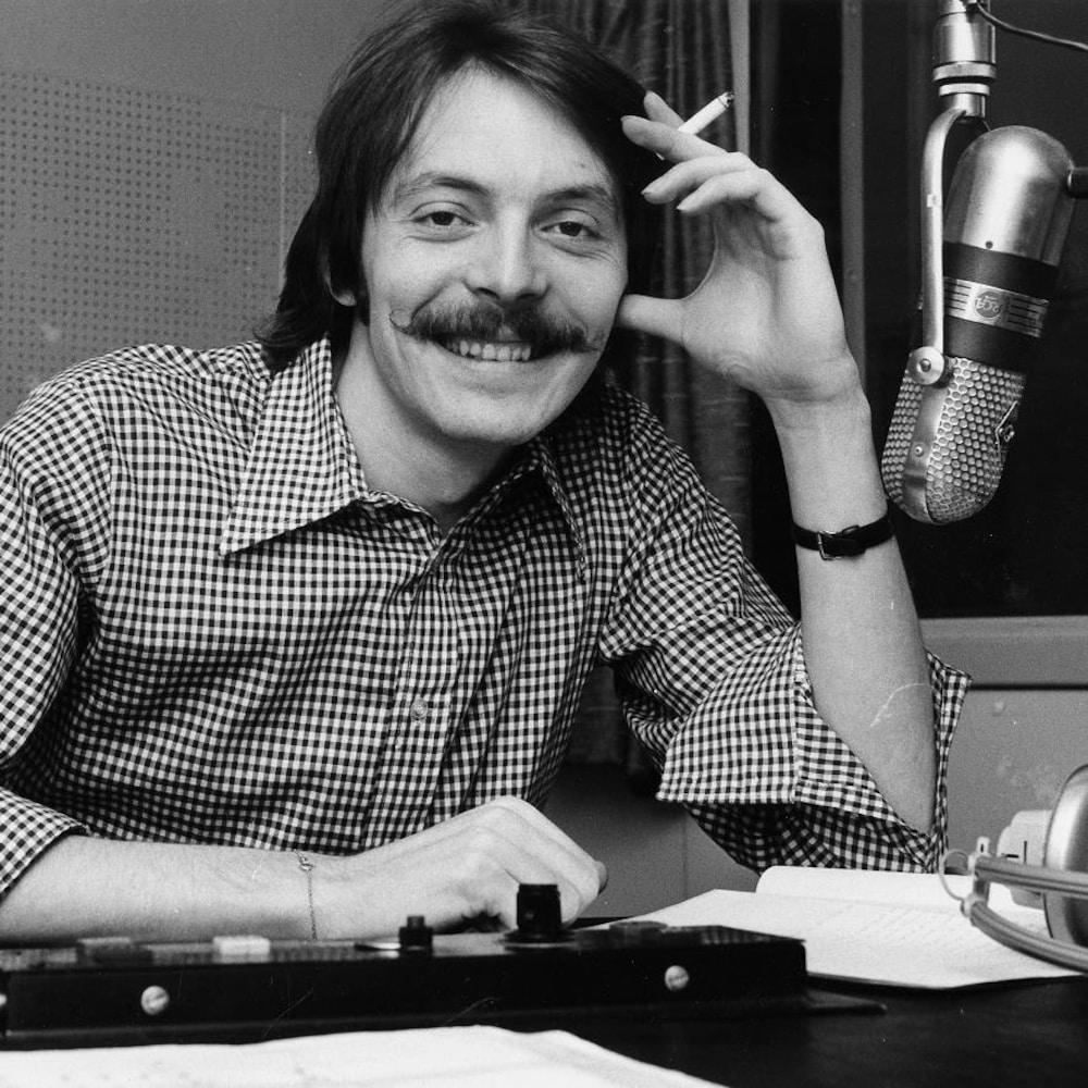 Dans un studio de radio de la station CJBC, à Toronto, l'animateur Michel Désautels, assis à une table derrière un micro suspendu, avec une cigarette à la main.