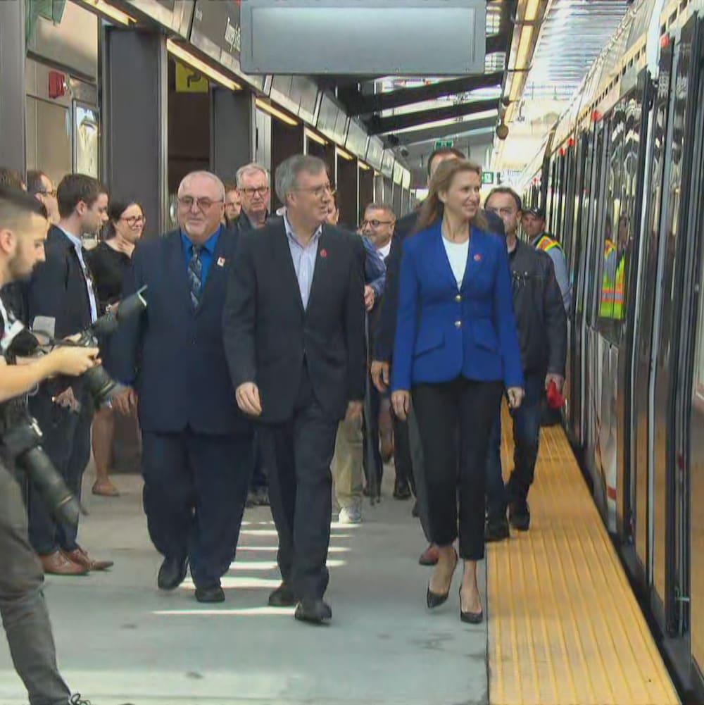 Jim Watson et Caroline Mulroney se dirigent vers un wagon du train léger d'Ottawa.