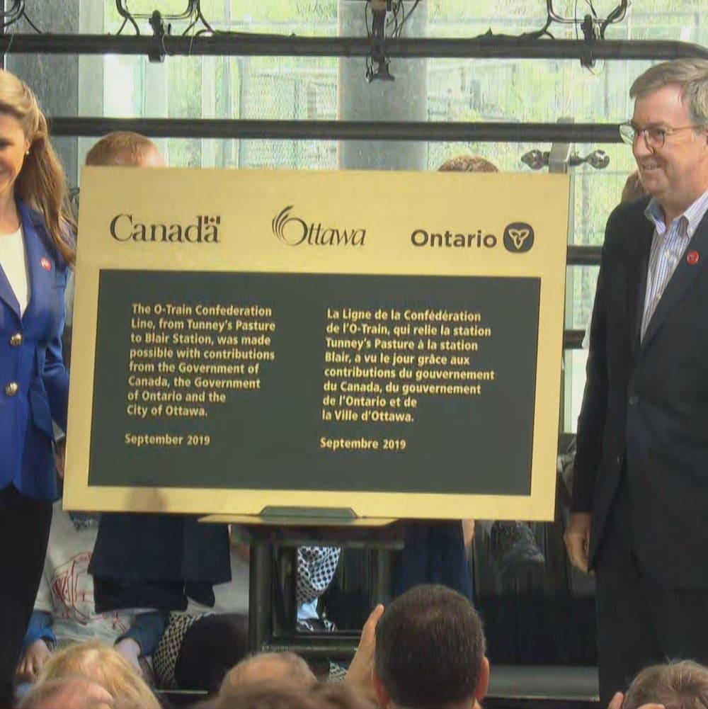 Caroline Mulroney et Jim Watson de part et d'autre d'une plaque commémorant l'ouverture du train léger d'Ottawa.