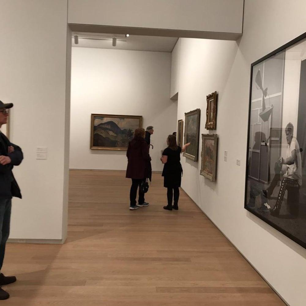 Des gens devant des tableaux