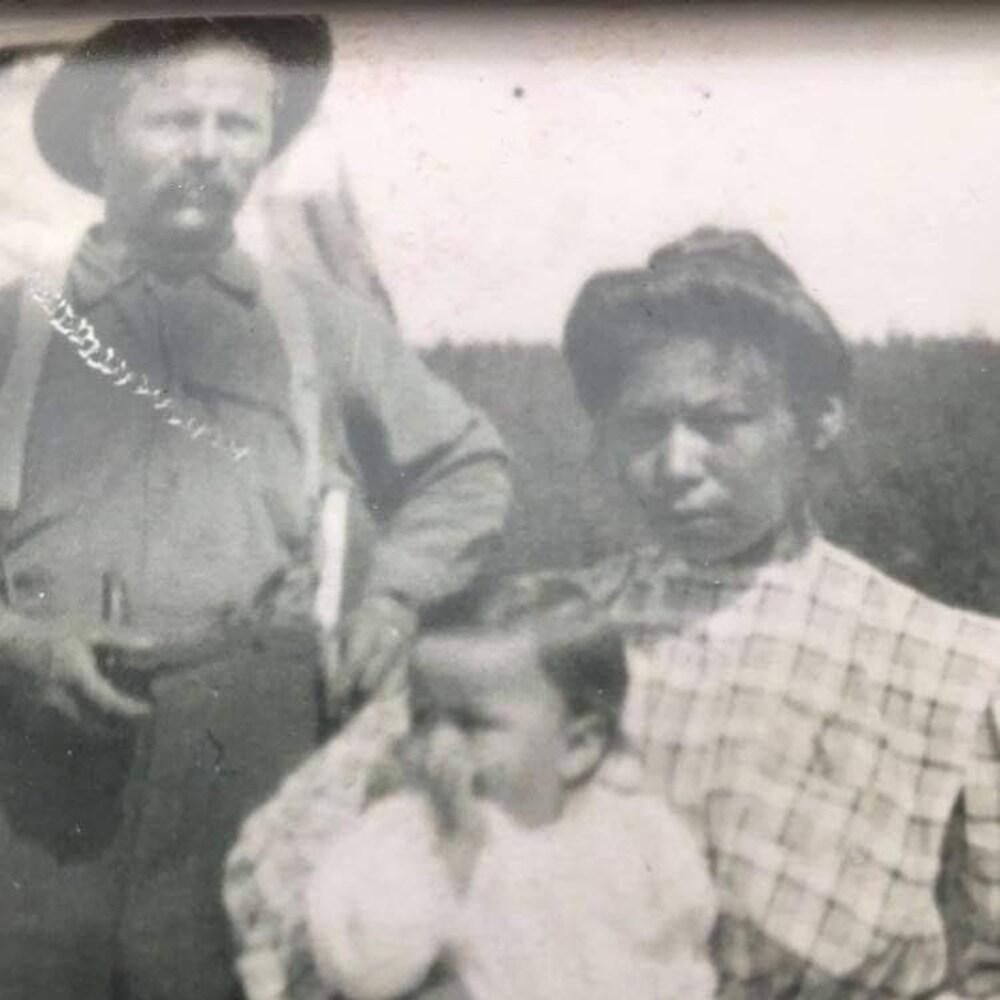 Un couple et son enfant prennent la pose devant une caméra.