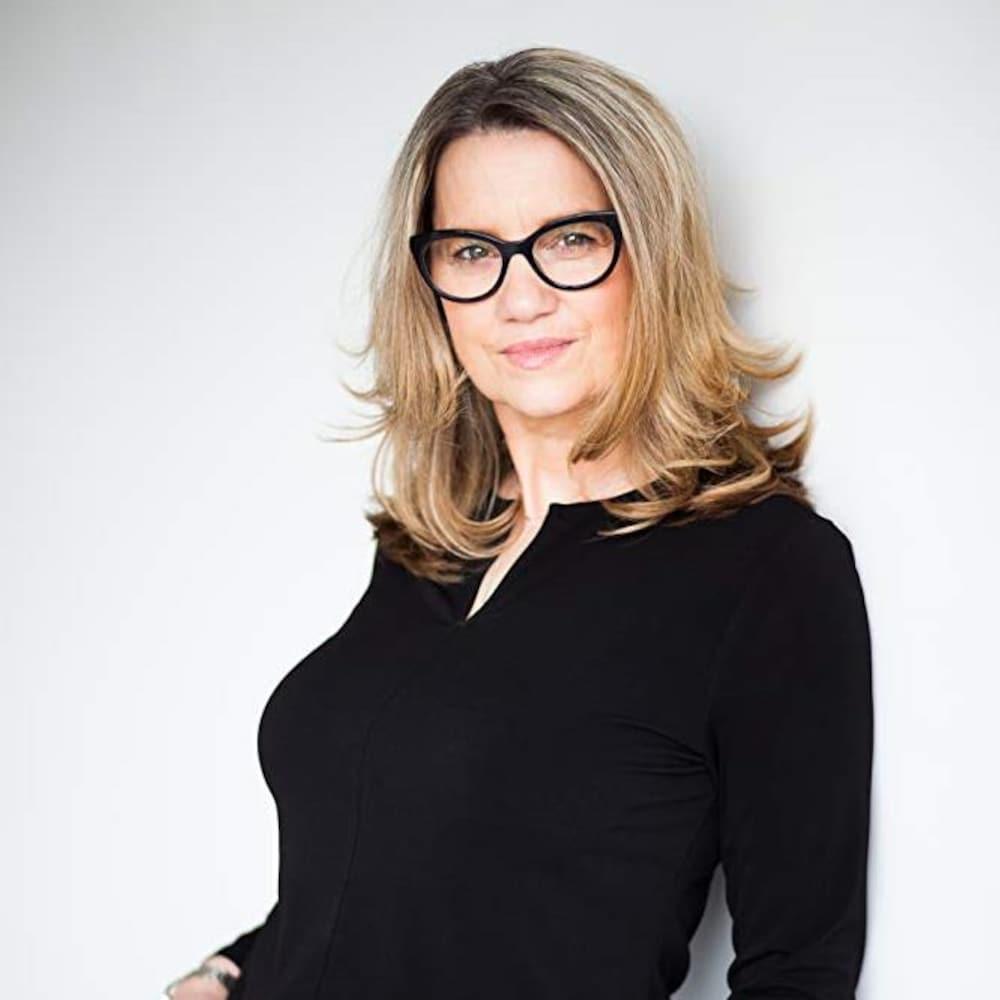 Une femme blancge portant des lunettes noires, debout devant un fond blanc et les mains dans les poches, regarde vers la caméra en souriant.
