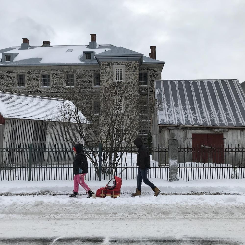 Deux adultes avec un enfant dans un traineau.