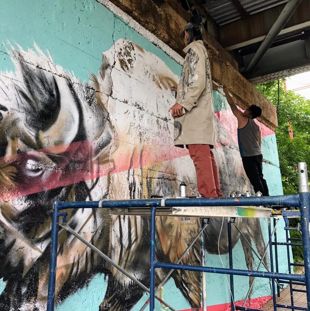 Les artistes Nereo II et John Padua en pleine création de l'oeuvre inaugurée le 1er juillet à La Fourche à Winnipeg.