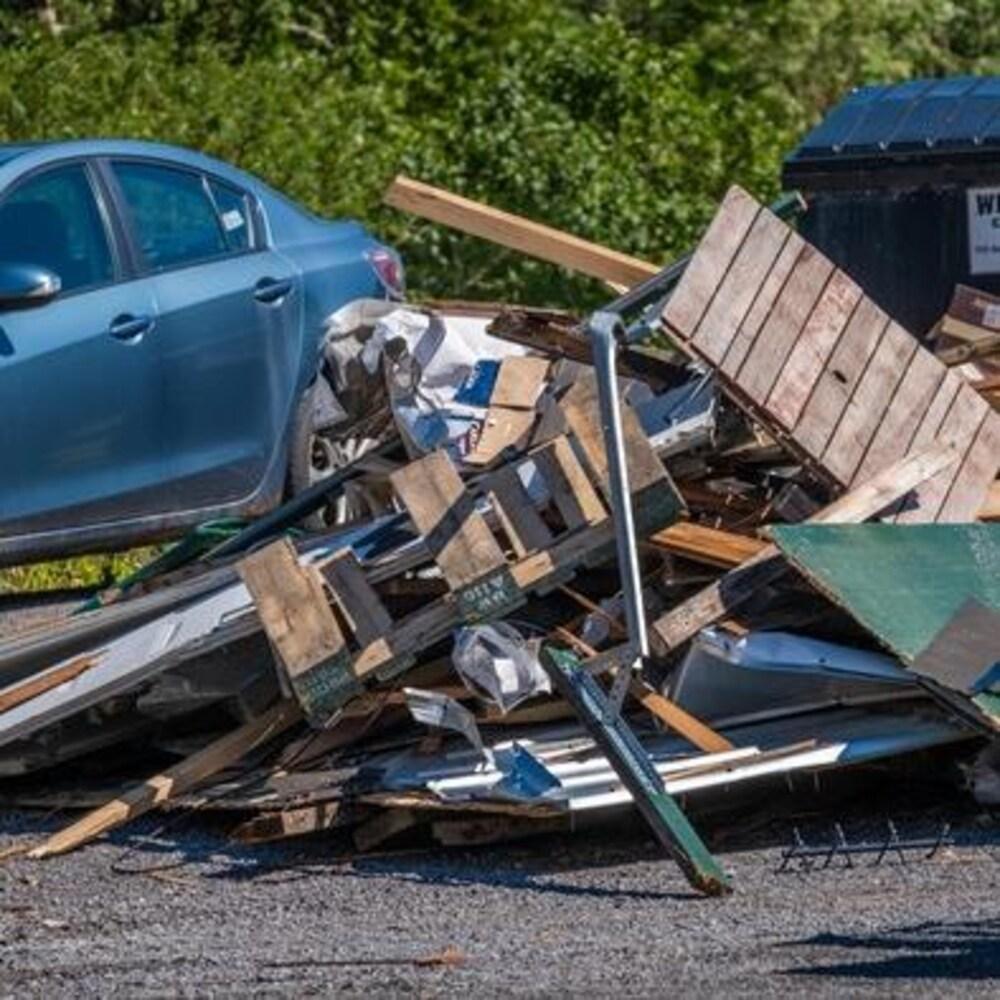 Un tas de débris jonchent le sol devant un conteneur à déchet plein.