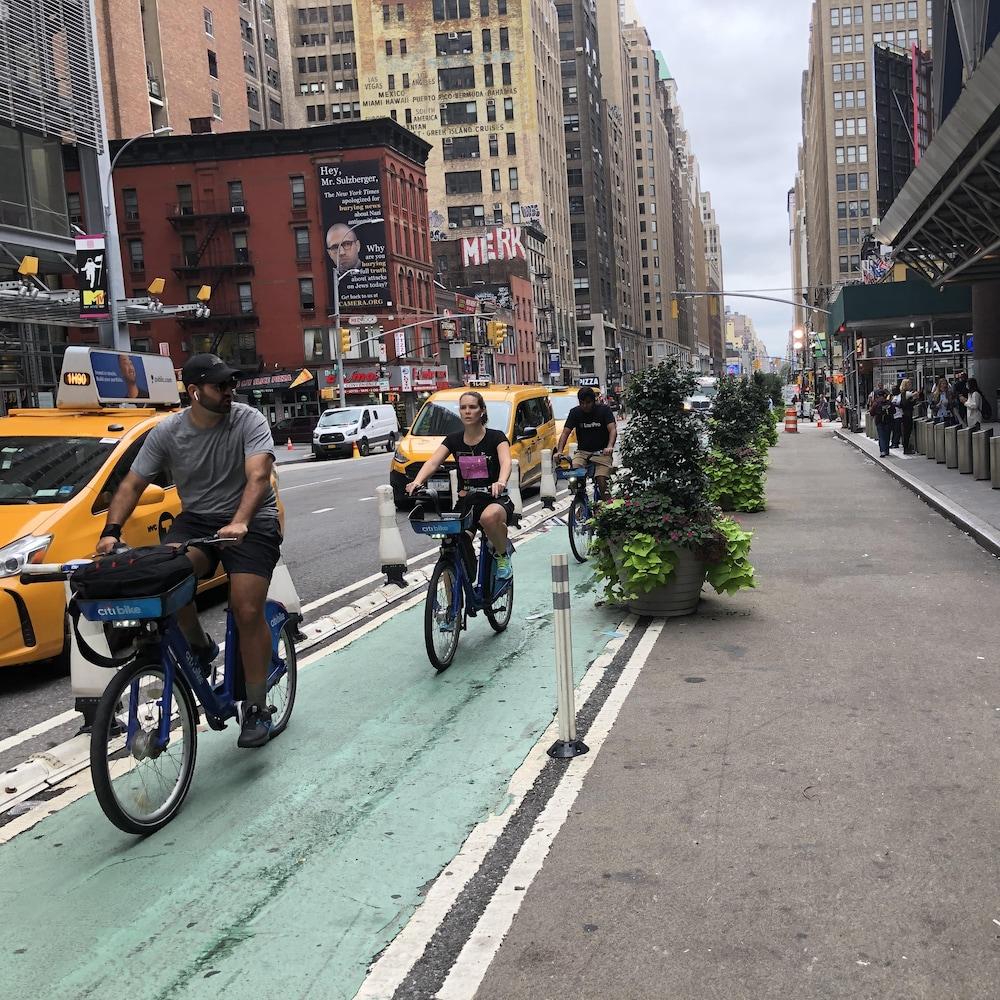 3 cyclistes sur une piste cyclable d'une grande rue de Manhattan.