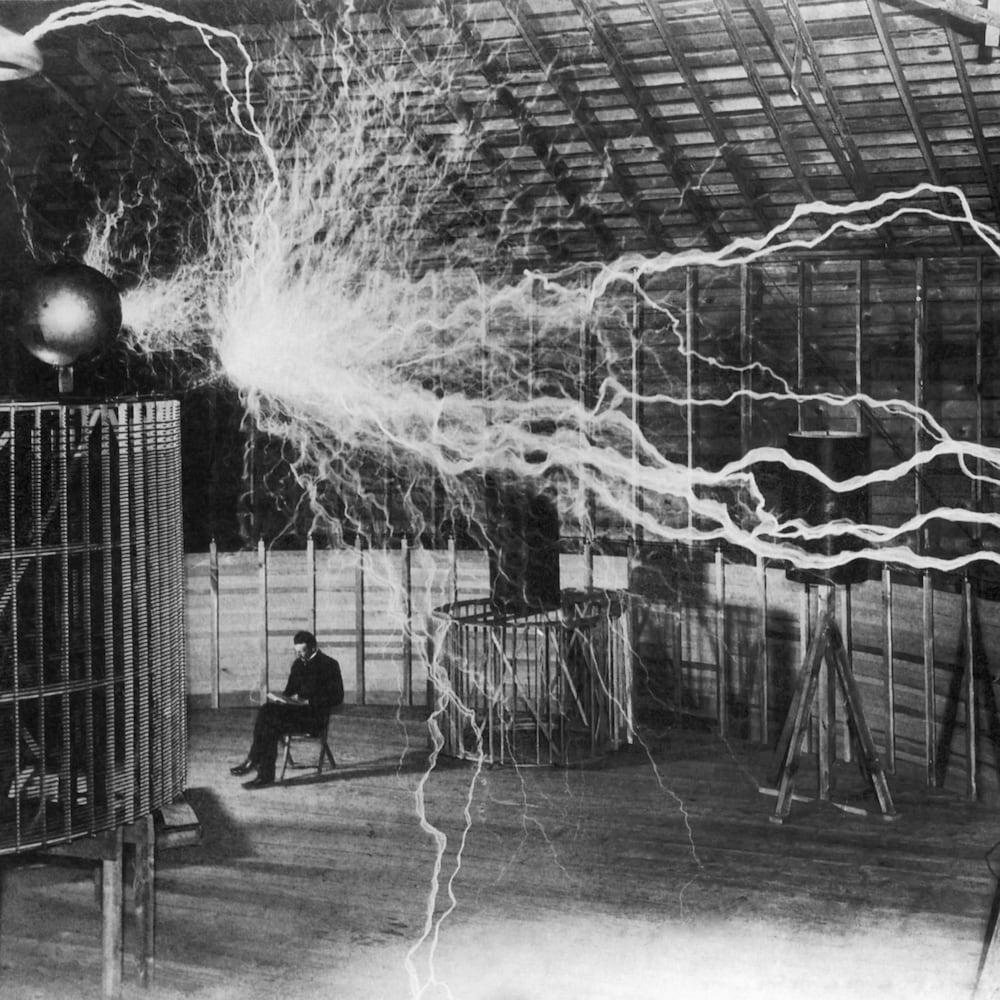 Nikola Tesla assis dans son laboratoire tandis que des éclairs électriques sont diffusés dans la pièce.