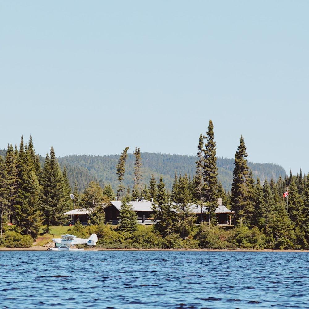 Le chalet est en bordure d'un lac. On aperçoit, au travers des conifères, un chalet en bois rond à un étage.