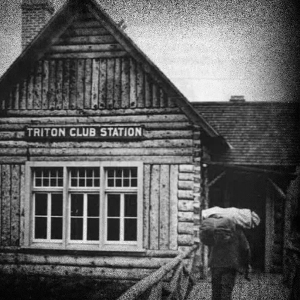 """La gare de train est une maison en bois rond avec une enseigne """"Triton Club Station""""."""