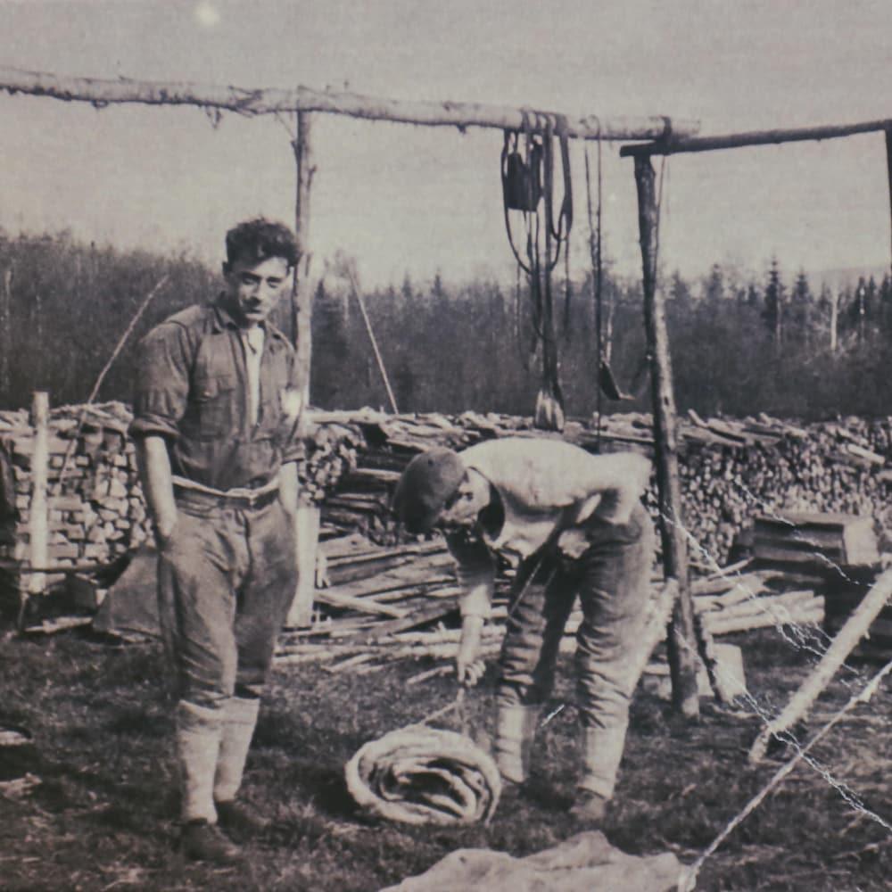 Image ancienne de deux hommes qui travaillent dans le bois.