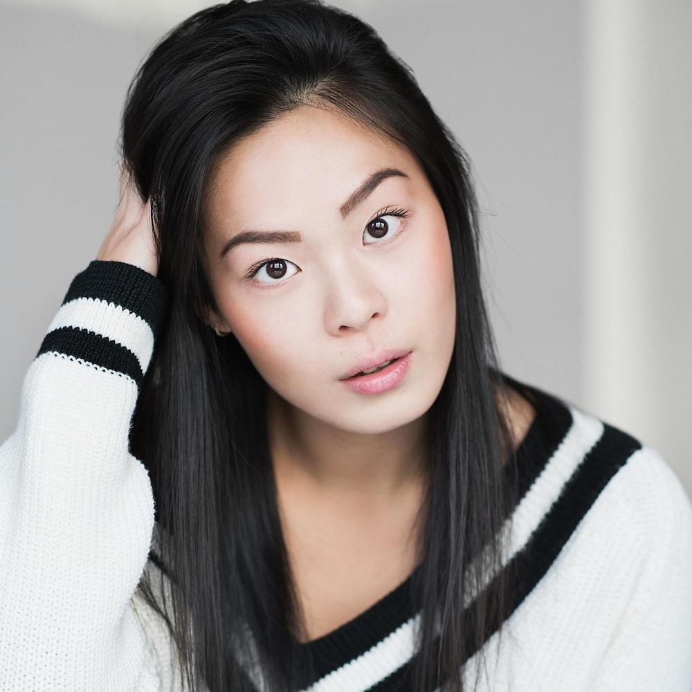 Une jeune femme, d'origine Chinoise, regarde vers la caméra.