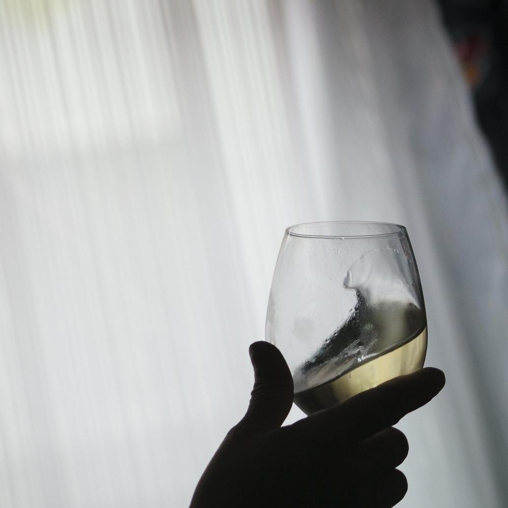 Une personne regarde une coupe de vin.